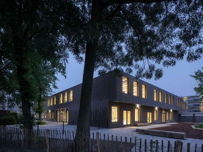 фасад деревянной школы вечером