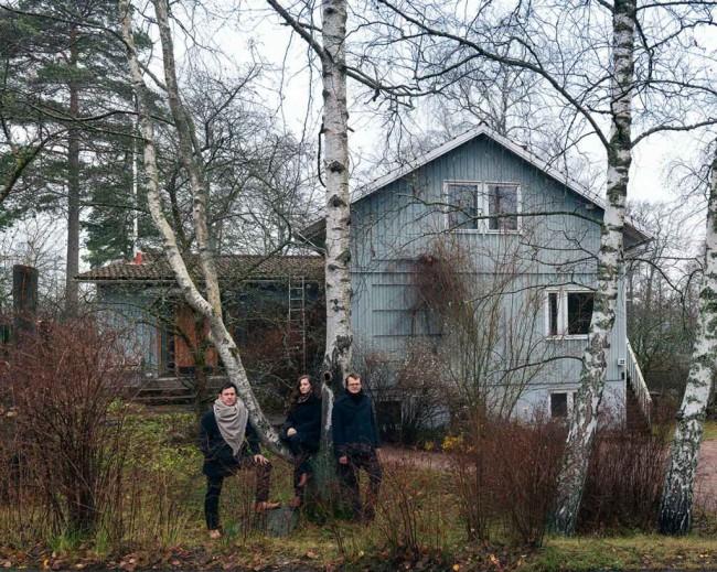 кураторы павильона Финляндии на биеннале в Венеции 2020 на фоне сборного деревянного дома