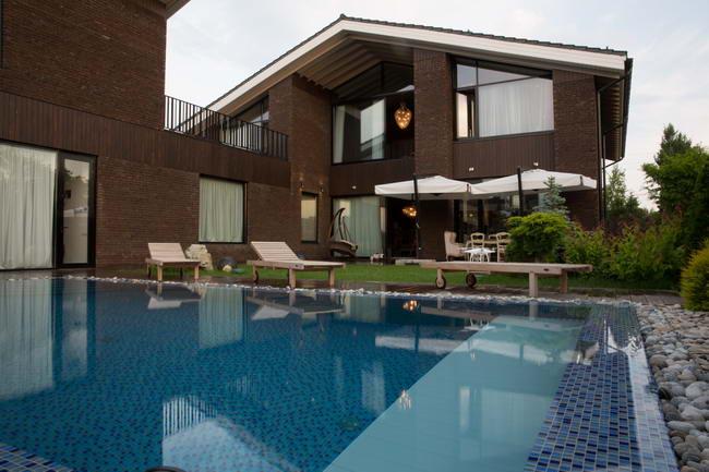 фасад кирпичного дома с бассейном