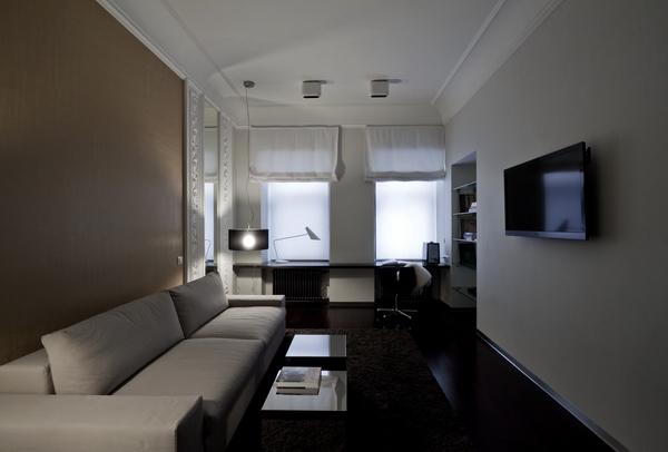 фотография интерьера с диваном и рабочим столом у окон